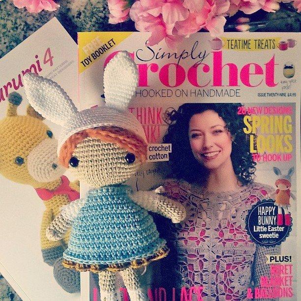 Bambola uncinetto amigurumi vestita da coniglietto di pasqua alla ricerca delle uova, con cappello con orecchie, vestito e zaino.