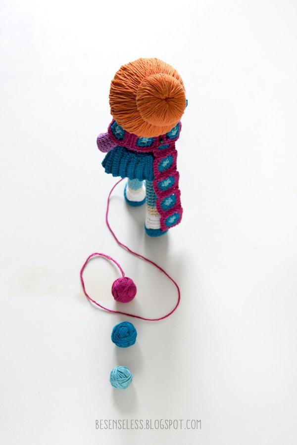 bambola amigurumi all'uncinetto che lavora con gomitoli e uncinetti