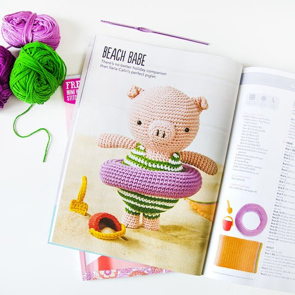 Amigurumi pig with crochet striped swimsuit, life ring, beach towel, bucket and spade on the beach on vacation. Airali design for Simply Crochet