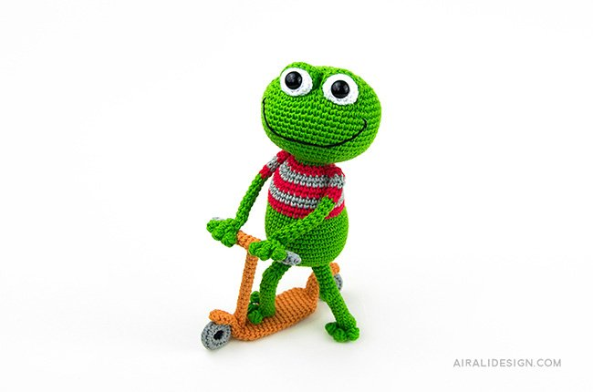 Frog riding a scooter. Crochet pattern from the book Amigurumi Globetrotters by Ilaria Caliri
