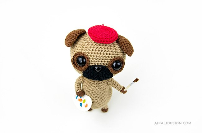 Artist Pug with red hat basque, paintbrush and palette. Crochet pattern from the book Amigurumi Globetrotters by Ilaria Caliri