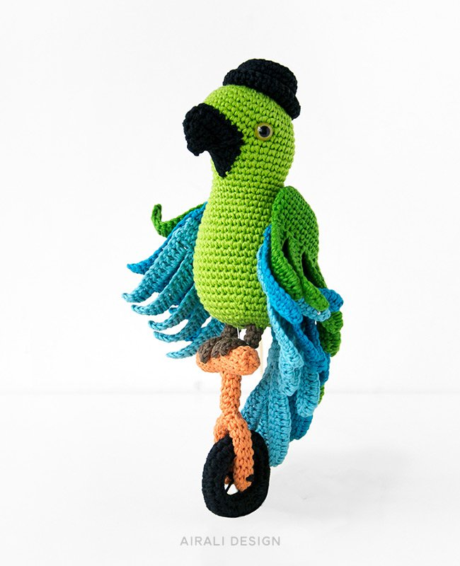 Carlo the amigurumi parrot with bowler hat on a unicycle, crochet pattern by Airali design